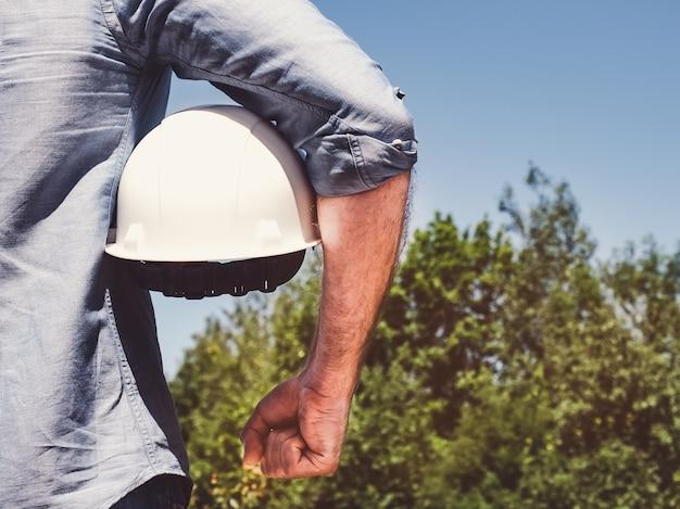 エンジニアは、公園で白いヘルメットを保持