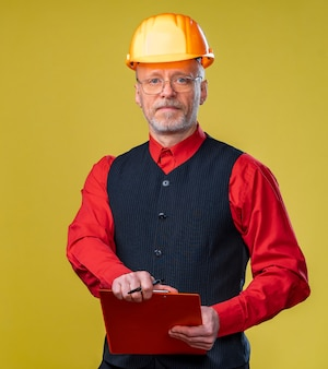 Инженер в каске на желтом фоне. старший мужчина держит буфер обмена.