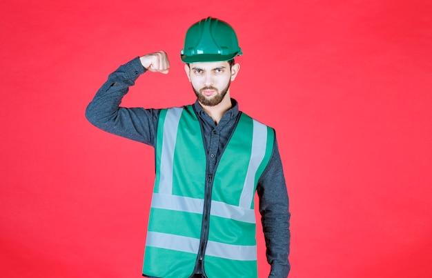 Инженер в зеленой форме и шлеме демонстрирует кулак.