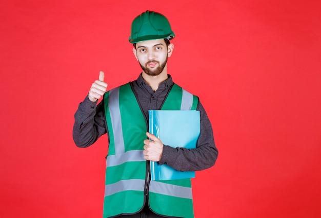 녹색 유니폼과 헬멧을 쓴 엔지니어는 파란색 폴더를 들고 긍정적인 손 기호를 보여줍니다.
