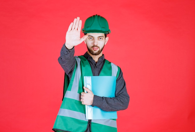 Инженер в зеленой форме и шлеме держит синюю папку и кого-то останавливает.