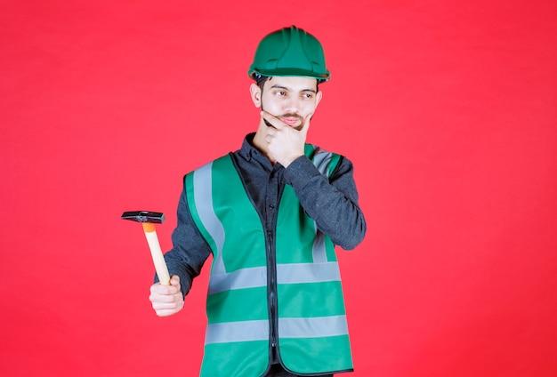 Инженер в зеленой форме и шлеме держит деревянный топор и думает.