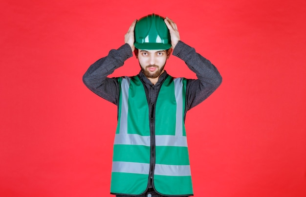緑の制服を着たエンジニアと、疲れたときに頭を抱えたヘルメット。