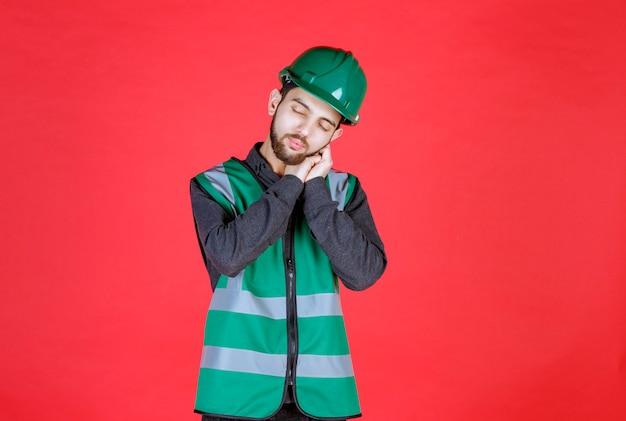 녹색 유니폼과 헬멧을 쓴 엔지니어는 피곤하고 졸려 보입니다.