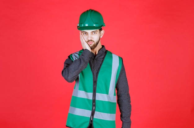 緑の制服とヘルメットのエンジニアは疲れて眠そうに見えます。