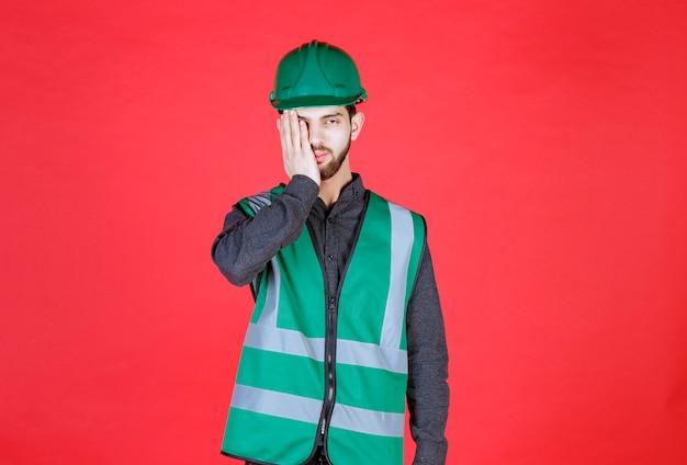 Инженер в зеленой форме и шлеме выглядит усталым и сонным.