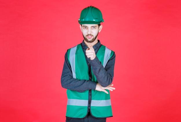 Инженер в зеленой форме и шлеме замечает человека впереди.