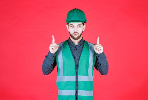 Инженер в зеленой форме и шлеме показывает вверху.