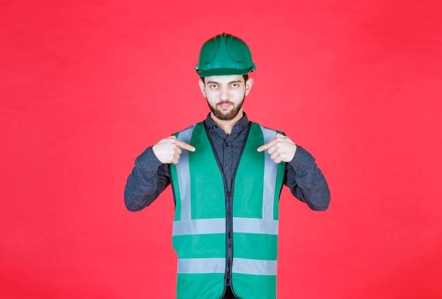 Инженер в зеленой форме и шлеме, указывая на себя.