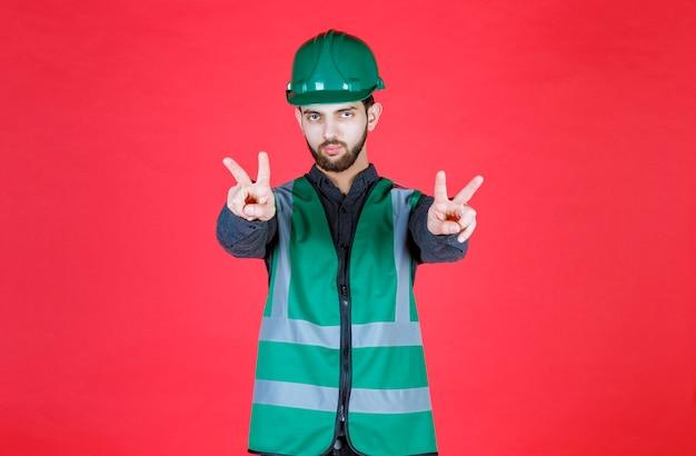 Инженер в зеленой форме и шлеме посылает мир и дружбу.