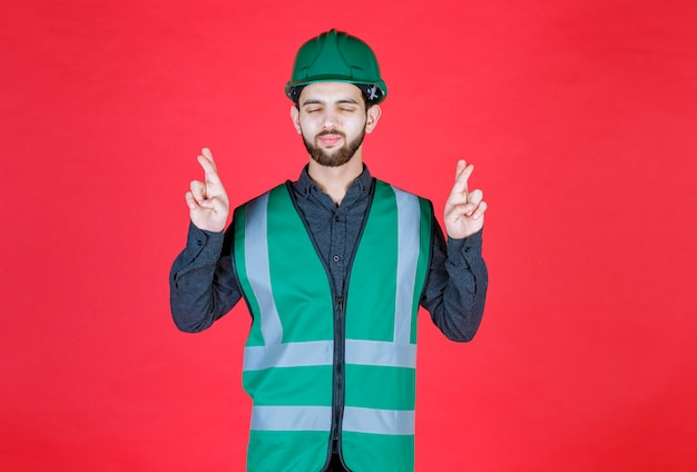 Инженер в зеленой форме и шлеме показывает знак креста пальца.