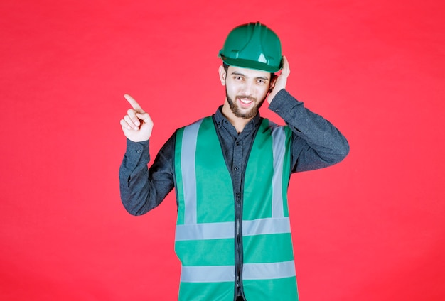 Инженер в зеленой форме и шлеме с левой стороны.