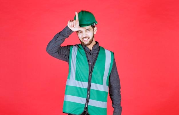 Инженер в зеленой форме и шлеме показывает знак проигравшего.
