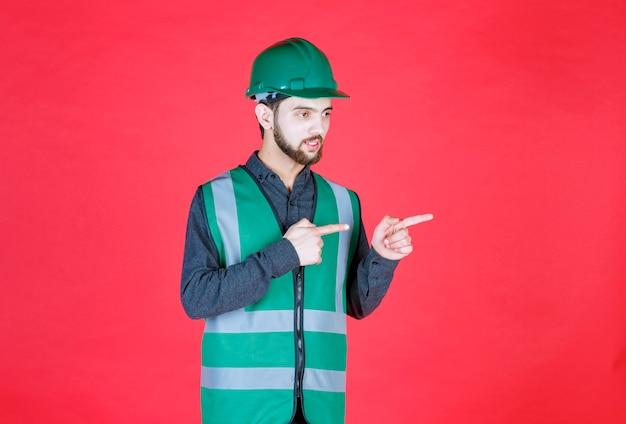 Инженер в зеленой форме и шлеме, показывающий правую сторону.