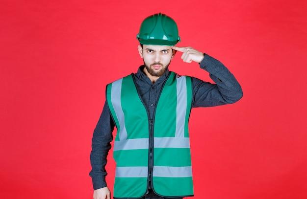 Инженер в зеленой форме и шлеме думает и планирует.