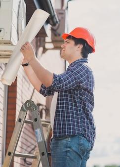 Инженер в каске смотрит в план системы кондиционирования воздуха.