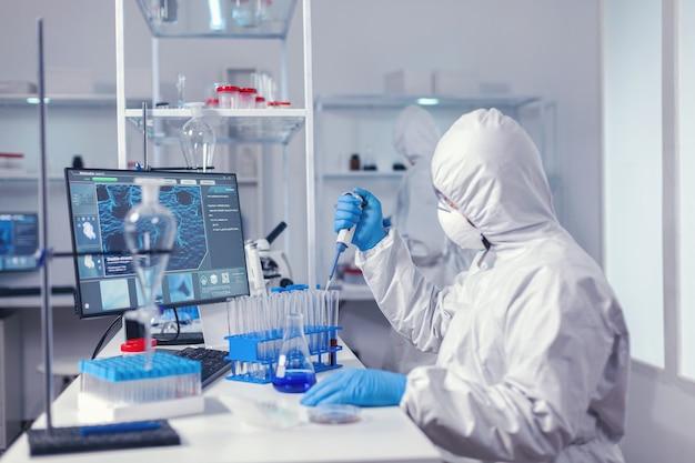 Инженер микробиологической лаборатории держит микропипетку с образцом из пробирки. химик в современной лаборатории проводит исследования с помощью дозатора во время глобальной эпидемии covid-19.