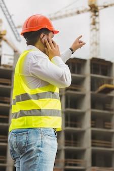 電話で話し、建築現場を指差して赤いヘルメットのエンジニア