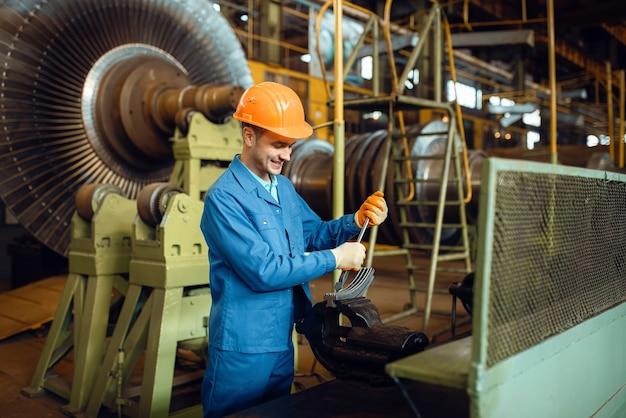 Инженер в форме и каске работает с деталью турбины на заводе, крыльчаткой с лопатками. промышленное производство, слесарное дело, производство силовых машин.