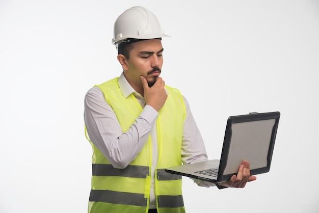 노트북을 들고 생각 하 고 제복을 입은 엔지니어.