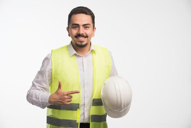 흰색 헬멧을 들고 제복을 입은 엔지니어.