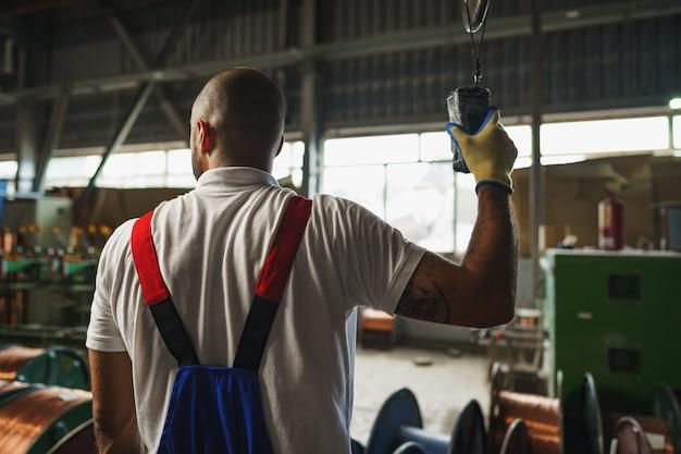 공장 천장에 매달린 크레인 컨트롤러를 사용하여 제복을 입은 엔지니어