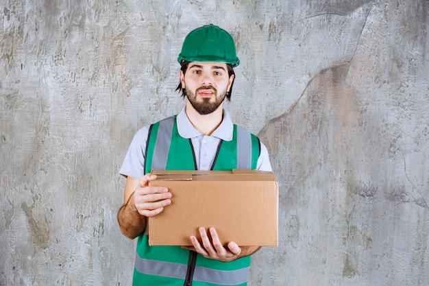 段ボール箱を持っている黄色いギアとヘルメットのエンジニアは、混乱して思慮深く見えます。