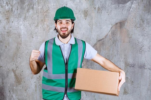 Инженер в желтой передаче и шлеме держит картонную коробку и показывает положительный знак рукой.