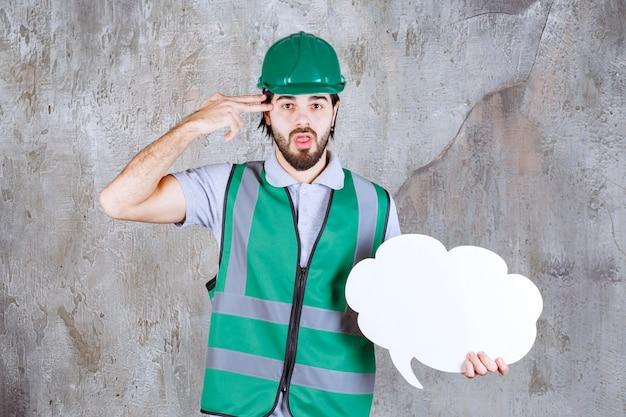 노란색 장비와 헬멧을 쓴 엔지니어는 구름 모양 정보 보드를 들고 사려 깊고 혼란스러워 보입니다.