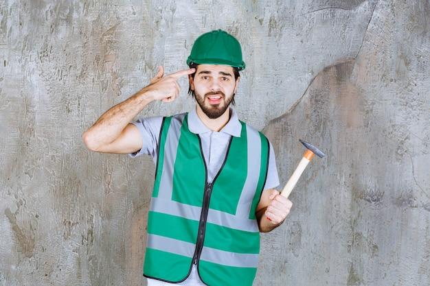 木製の柄の斧を持っている黄色いギアとヘルメットのエンジニアは混乱しているように見えます。