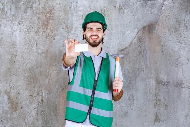Инженер в желтой экипировке и шлеме держит топор с деревянной ручкой и представляет свою визитную карточку.
