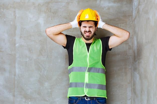 彼は頭痛を持っているので彼のヘルメットを脱ぐことを試みている黄色いヘルメットと工業用手袋のエンジニア