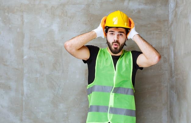 노란색 마스크와 산업용 장갑을 낀 엔지니어는 혼란스럽고 겁에 질려 보입니다.