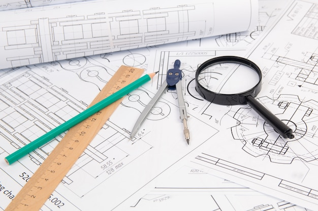 Engineer industrial chain drawings, engineering compass, magnifying glass, ruler and pencils