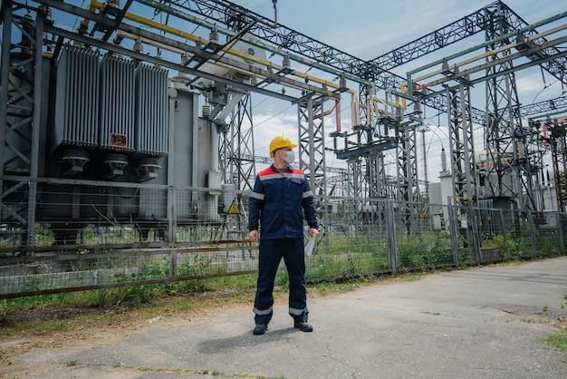 Инженер осматривает оборудование подстанции