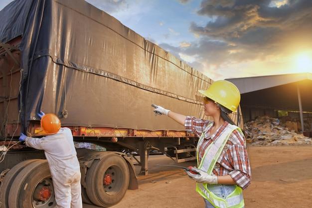 Инспектор-инженер, работающий на грузовике с фоном контейнера. бизнес концепции логистики и транспорта.