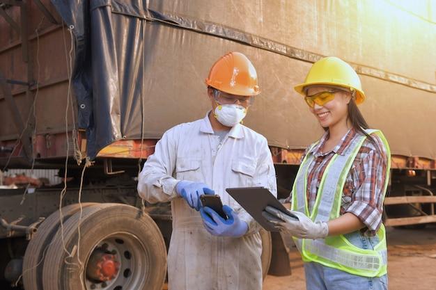 コンテナーの背景を持つトラックで働くエンジニアの検査官。物流と輸送の概念のビジネス。