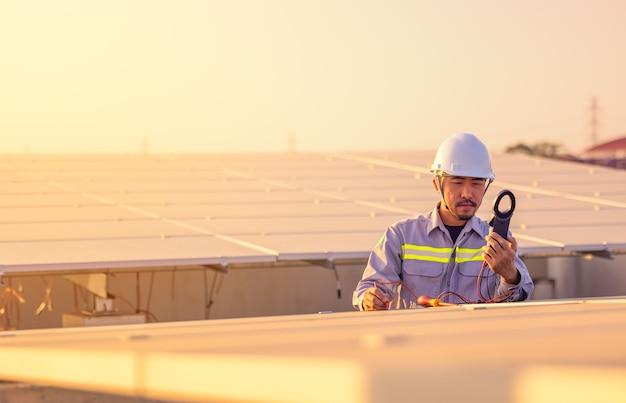 エンジニアは、現代の家の屋根にあるソーラーパネルを検査します。代替エネルギーの生態学的概念。