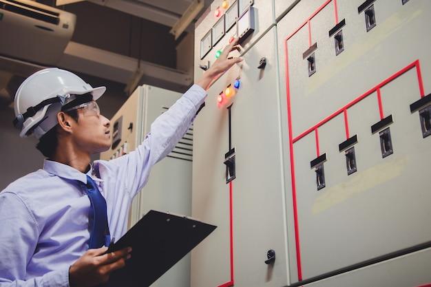 エンジニアは、発電所のコントロールパネルの電圧計で電圧または電流を確認しています。