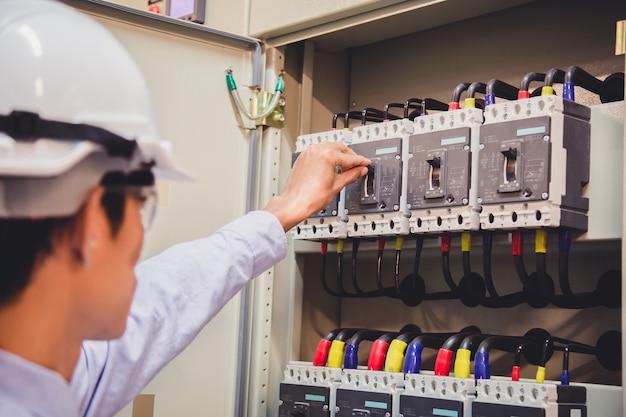エンジニアは、発電所のコントロールパネルの電圧計で電圧または電流を確認しています。 Premium写真