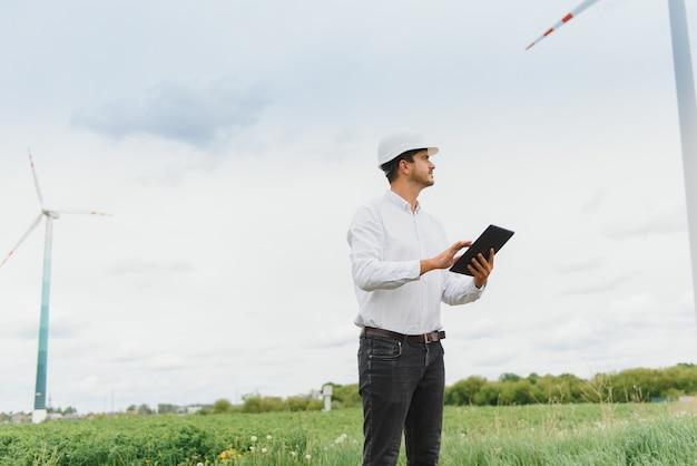 Инженер проверяет выработку энергии на ветряной турбине. работник в парке ветряных мельниц в шлеме и с таблеткой.