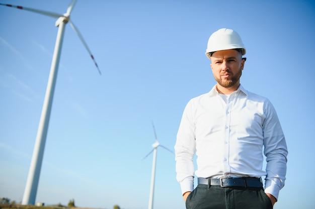 Инженер проверяет выработку энергии на ветряной турбине. работник в парке ветряных мельниц в шлеме.