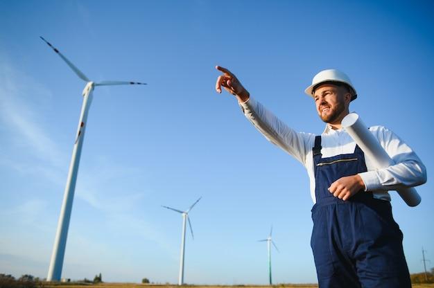 엔지니어가 풍력 터빈의 에너지 생산을 확인하고 있습니다. 헬멧에 풍차 공원에서 노동자입니다.