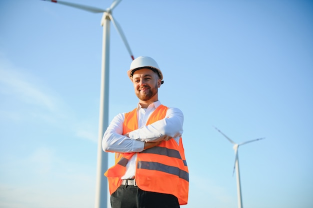 Engineer is checking energy production on wind turbine. worker in windmills park in helmet.