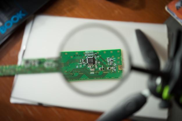 Ingegnere che esamina un circuito stampato attraverso una lente di ingrandimento