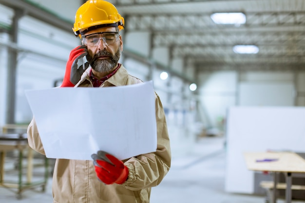 Engineer looking at plan in the factory
