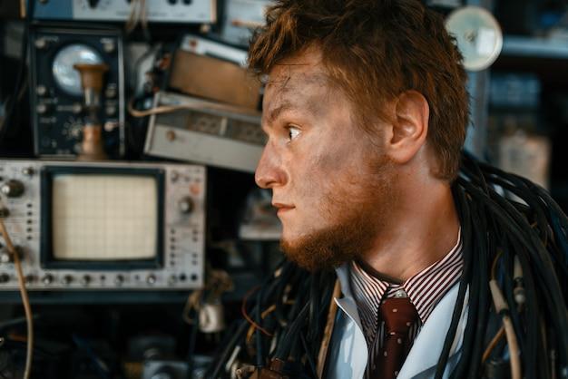 Инженер смотрит на дисплей осциллографа в лаборатории