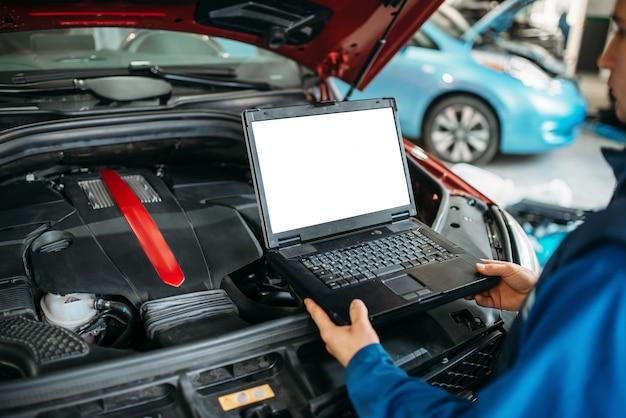 Engineer makes computer diagnostics of car engine