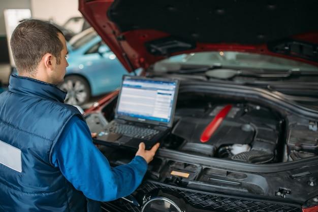 Инженер производит компьютерную диагностику двигателя автомобиля.
