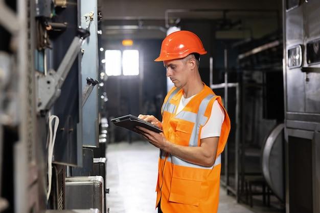 디지털 태블릿 검사 및 프로그램을 사용하여 공장 전기 엔지니어에서 일하는 남성 엔지니어